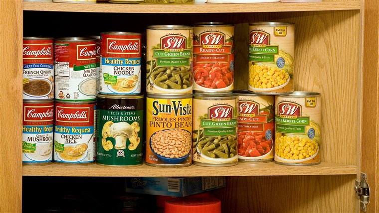 Kayu kitchen cupboard with shelves full of canned soup and vegetables