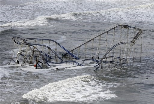 Di this Wednesday, Oct. 31, 2012 file photo, waves wash over a roller coaster from a Seaside Heights, N.J. amusement park that fell in the Atlantic