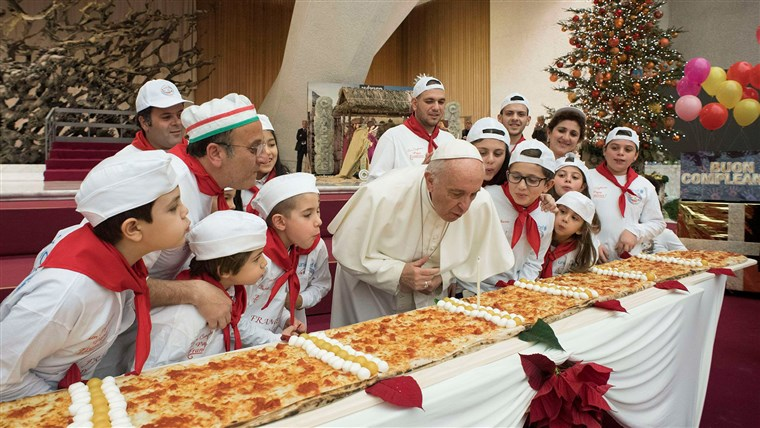 Gambar: Pope Francis blows on a cake to celebrate his birthday during a special meeting at Paul VI hall at the Vatican
